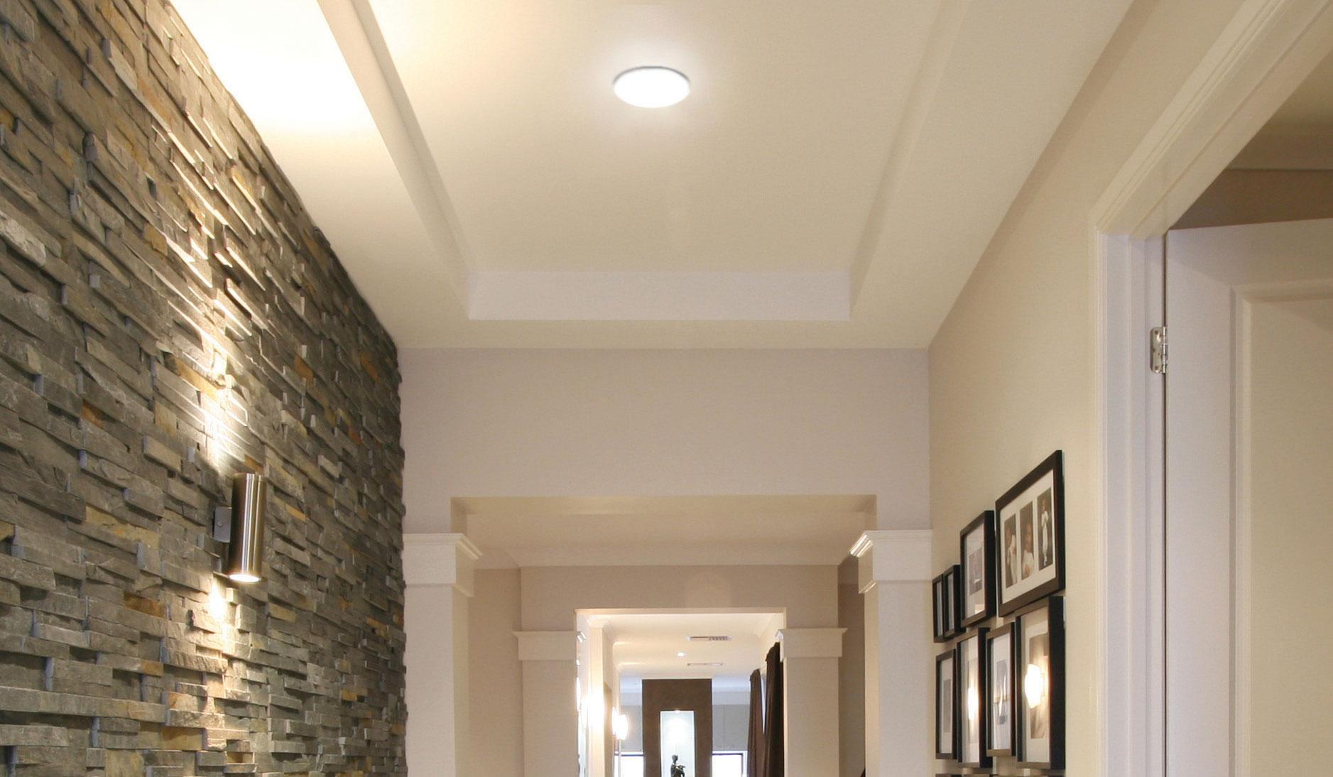 Luminaire plafonnier traditionnel DEL Standard 64154 éclairant une entrée avec mur de brique et cadres
