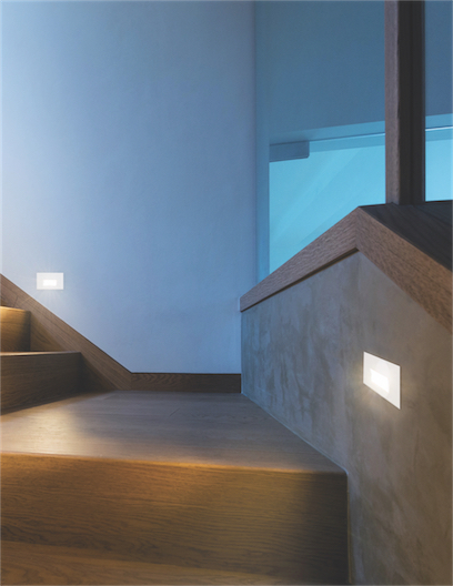 Outdoor step light Kuzco ER3005-BK lit in the wood stairs