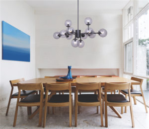 Luminaire suspendu moderne ATLAS Canarm  IPL741A12BK9 au-dessus de la table de salle à manger en bois près d'une grande fenêtre avec bibelot et cadre bleu.